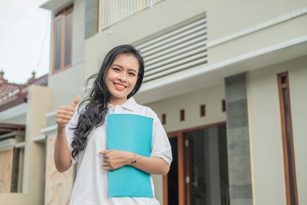 Imprenditore edile donna asiatica azienda certificato di casa con i pollici in su davanti alla casa
