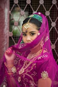 Donna asiatica in un sari di tradizione indiana sta guardando in basso a lato una porta in ferro battuto