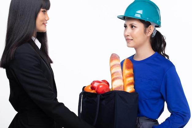 La donna asiatica è il servizio di consegna del cibo, la femmina invia il pane e la frutta nella borsa del tessuto e sorride alla donna di affari dell'ufficio, lo spazio della copia isolato sfondo bianco