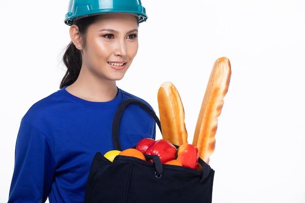 La donna asiatica è il servizio di consegna del cibo, la femmina invia il pane e la frutta nella borsa e nel sorriso del tessuto, spazio della copia isolato fondo bianco