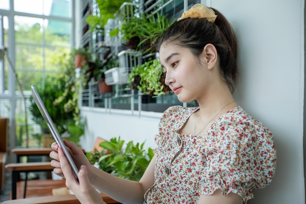 La donna asiatica sta utilizzando la tavoletta digitale per leggere le notizie e fare acquisti online in giardino a casa in un momento di relax