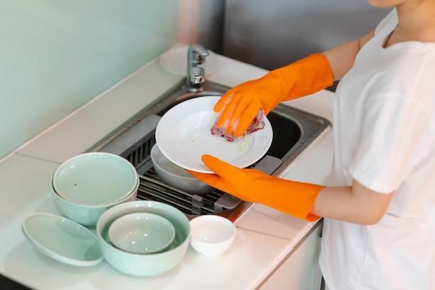 La donna asiatica sta lavando i piatti
