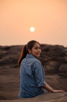 Donna asiatica in camicia di jeans seduto e rilassante in cima alla scogliera al tramonto nel parco nazionale