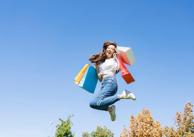 Donna asiatica che salta con i sacchetti della spesa