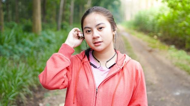 Donna asiatica che ascolta la musica dopo aver eseguito nella foresta