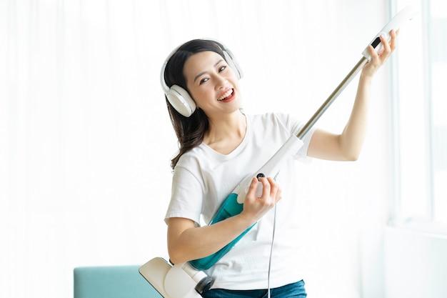 Donna asiatica che ascolta la musica e balla con un aspirapolvere