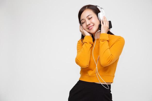 Musica d'ascolto della donna asiatica con le cuffie