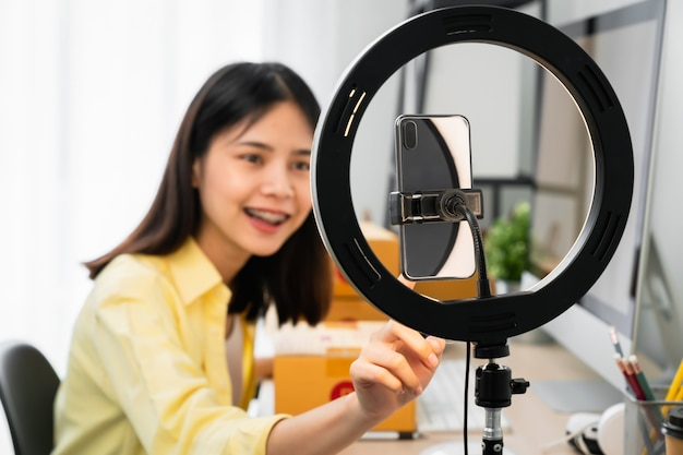 Trasmissione in diretta di donna asiatica su smartphone con vendita di prodotti online, piccole imprese di avvio.