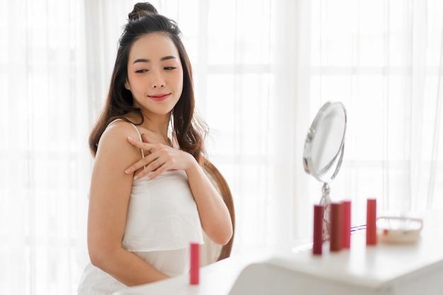 Donna asiatica guardando allo specchio applicare la crema a casa