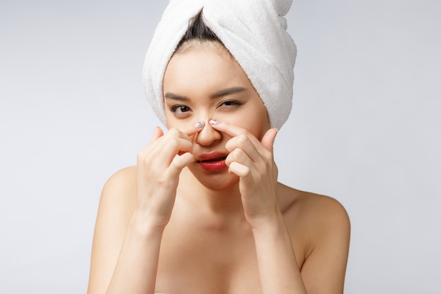 Donna asiatica guardando brufolo sul viso. la giovane donna prova a rimuovere il suo brufolo