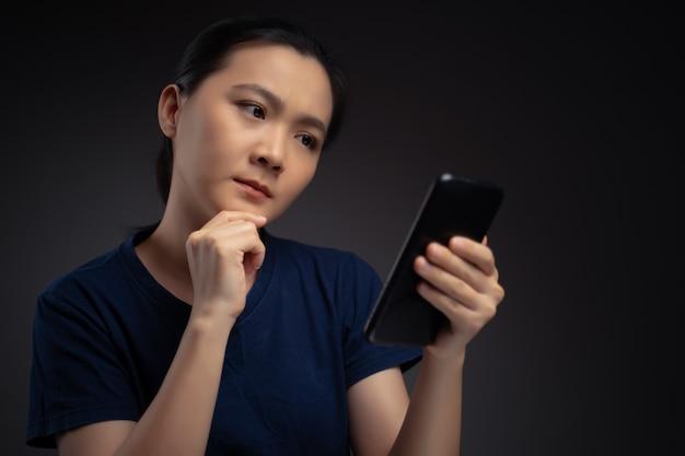 Donna asiatica che guarda le notizie di lettura dello smartphone e si sente confusa.