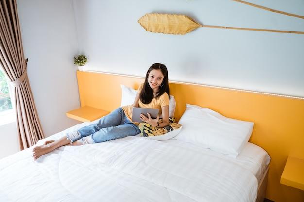 Donna asiatica sdraiata a letto con tavoletta digitale toccando con il dito nella luce del sole del mattino