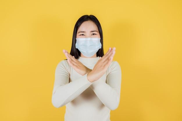 Donna asiatica in maschera medica per proteggere covid-19 (coronavirus), smettere di uscire su sfondo giallo, distanza sociale e quarantena sono importanti