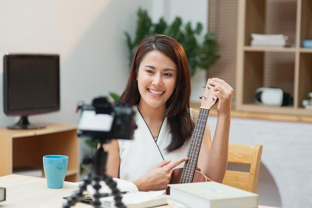 L'insegnante di musicista donna asiatica si siede in soggiorno a parlare con la telecamera che insegna la chitarra a casa