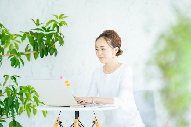 Donna asiatica che utilizza un laptop in una stanza luminosa