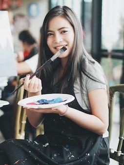 Donna asiatica nella classe di pittura
