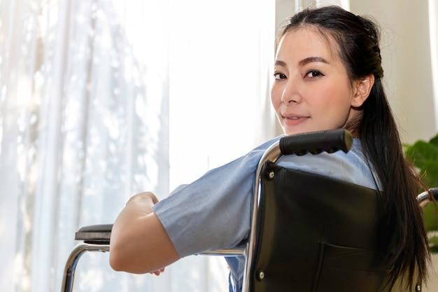 Seduta paziente della donna asiatica nella sedia a rotelle alla stanza di ospedale.