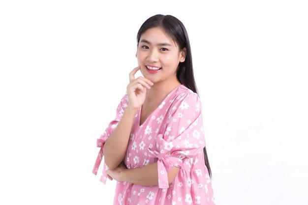 La donna asiatica in abito rosa e il sorriso lungo i capelli neri mostrano una bella pelle su sfondo bianco