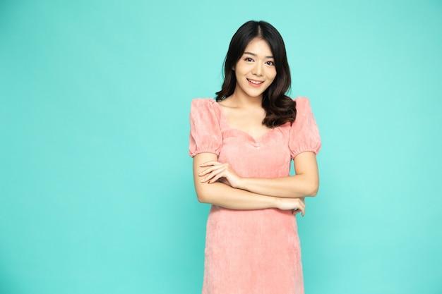 Donna asiatica in abito rosa con le braccia incrociate e il sorriso isolato su verde.