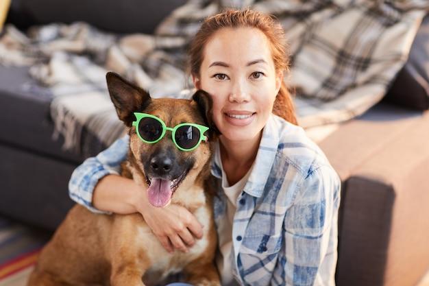Donna asiatica che propone con il cane divertente