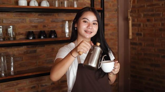 La donna asiatica versa il caffè in un bicchiere
