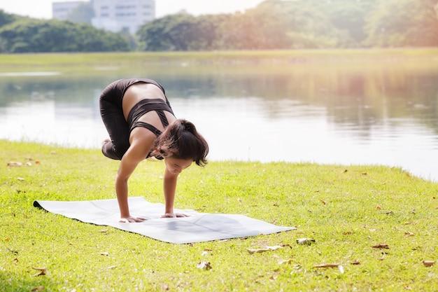 Donna asiatica che pratica yoga facendo posa della gru crow posa bakasana