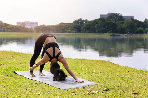 Donna asiatica che pratica yoga facendo posa del cane rivolto verso il basso adho mukha svanasana
