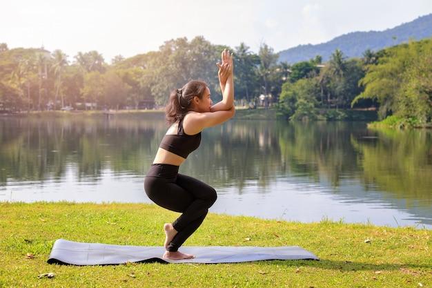 Donna asiatica che pratica yoga facendo posa di eagle pose sul tappeto accanto a un lago in un parco all'aperto.