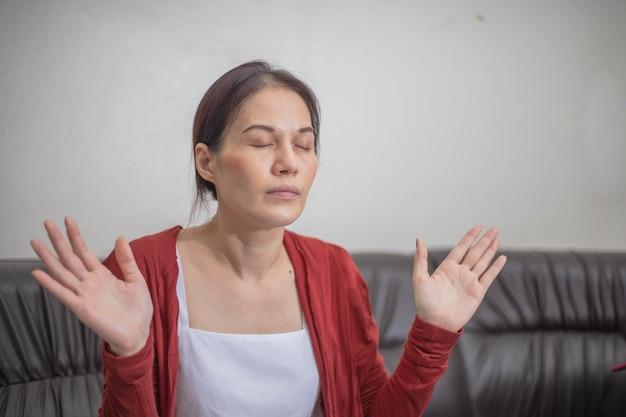 La donna asiatica prega e adora a casa, chiesa online, mani in preghiera, adorazione a casa.