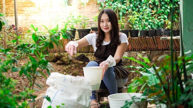 Donna asiatica preparare un posto per piantare con il vaso