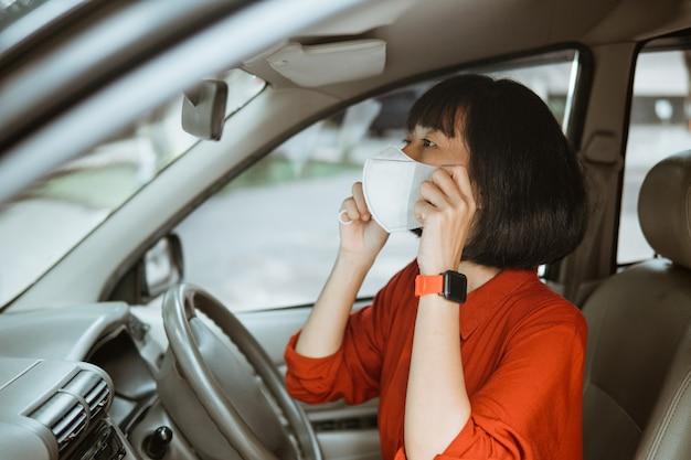 Donna asiatica in maschera protettiva alla guida di un'auto su strada. viaggio sicuro.