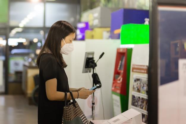 Donna asiatica in maschera protettiva utilizzando il codice qr di scansione del telefono cellulare.