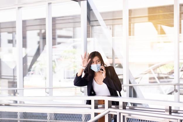La donna asiatica alza le mani incontro, felice saluto ai suoi amici all'aeroporto