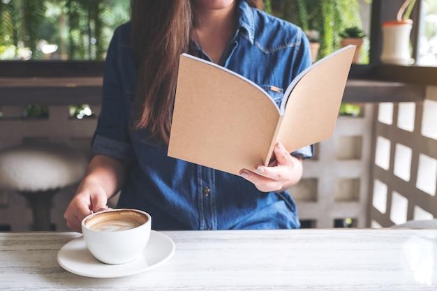 Donna asiatica che legge un libro mentre bevono caffè in caffè moderno