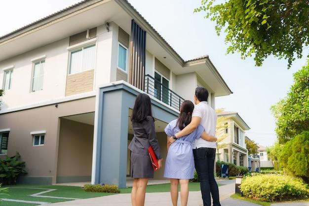 Donna asiatica agente di mediatore immobiliare che mostra un dettaglio della casa
