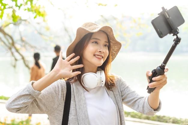Donna asiatica che registra video sulla strada ad hanoi, vietnam