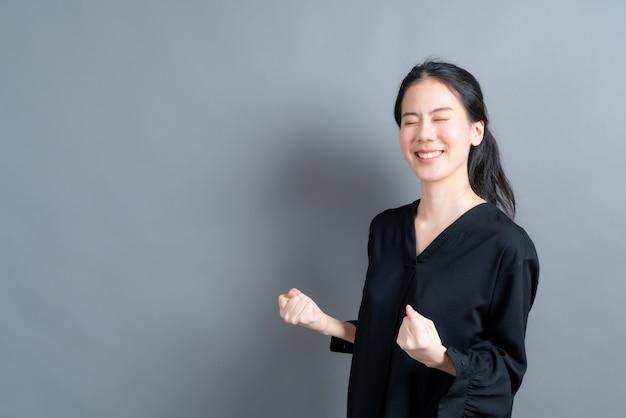 Donna asiatica che si rallegra del suo successo e della vittoria che stringe i pugni con gioia. donna fortunata che è felice di raggiungere il suo scopo e i suoi obiettivi. emozioni positive, sentimenti