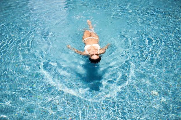 La donna asiatica si rilassa sulla piscina d'acqua in estate prende il sole felice in piscina e la suite bikini e gli occhiali da sole