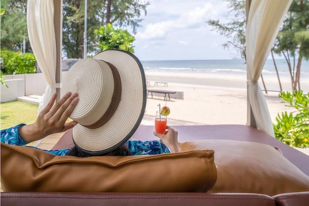 Una donna asiatica si è rilassata sulla spiaggia con il suo cocktail di ciliegie al lime rosso in mano durante la giornata estiva di apertura