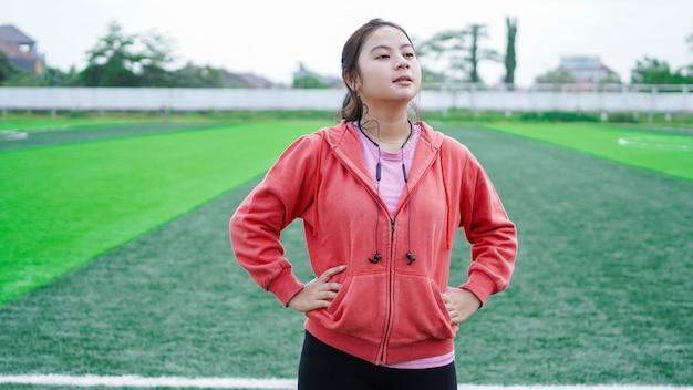 Riposo della donna asiatica dopo l'esecuzione. indossare giacca e auricolare