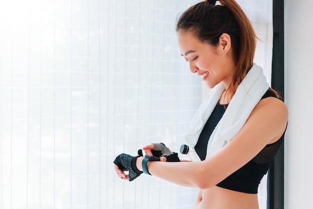 Donna asiatica che riposa e che utilizza orologio intelligente dopo aver giocato a yoga ed esercizio a casa sfondo con copia spazio.