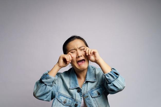 Donna asiatica triste e piangente in piedi isolato.