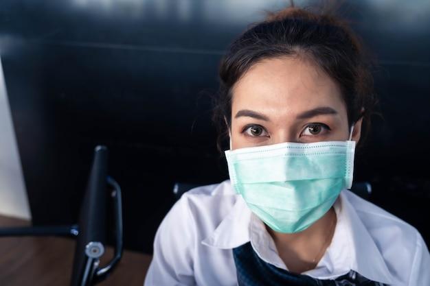 La donna asiatica saleman indossa la mascherina chirurgica che lavora nell'ispettore che controlla le notizie covid19