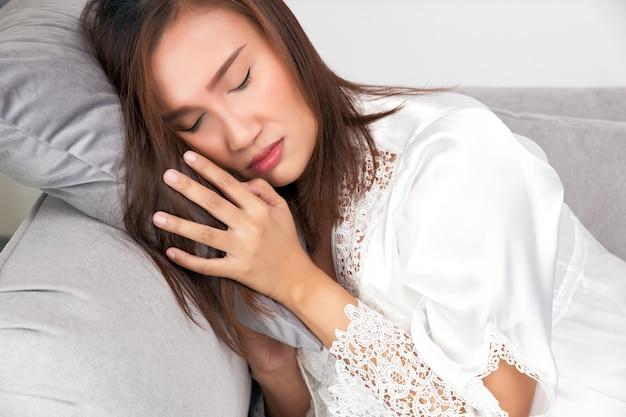 Donna asiatica in un pigiameria di raso con la faccia bianca e rossa a causa della febbre e della temperatura corporea febbrile