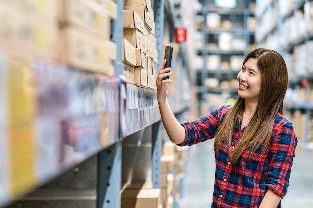 Donna asiatica che esplora il codice qr via telefono cellulare per il controllo delle scorte e del prezzo delle merci in magazzino