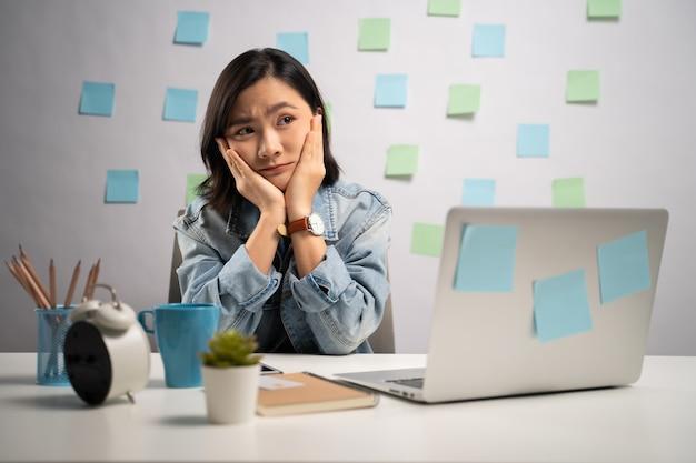 Donna asiatica che lavora seriamente su un computer portatile in ufficio a casa. . lavoro da casa. concetto di prevenzione coronavirus covid-19.