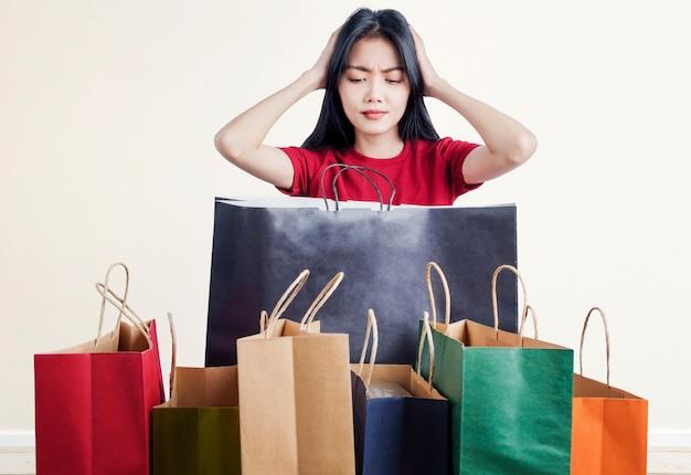 Donna asiatica scioccata con così tante borse della spesa con muro bianco