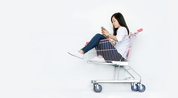 Donna asiatica che fa shopping sul cellulare seduto nel carrello della spesa