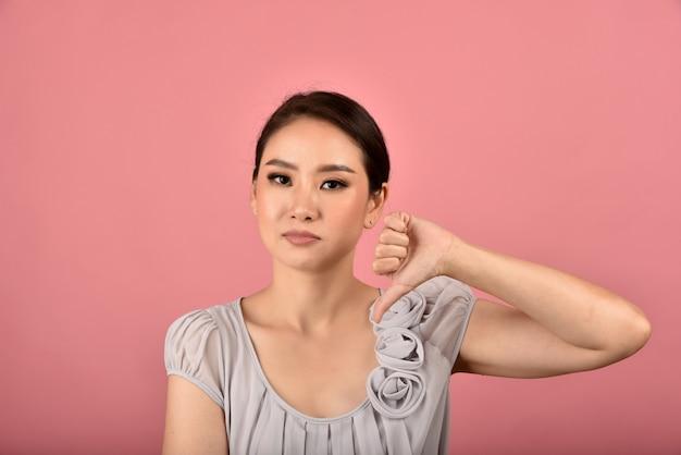Donna asiatica che mostra pollice verso il gesto, espressione infelice infastidita infastidita insoddisfatto scontroso, segno di antipatia.