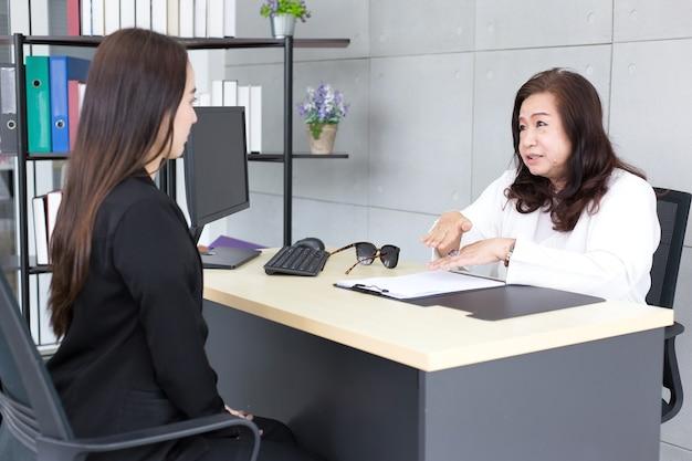 La donna asiatica si siede sulla sedia durante il colloquio di lavoro con il direttore aziendale nella stanza dell'ufficio.